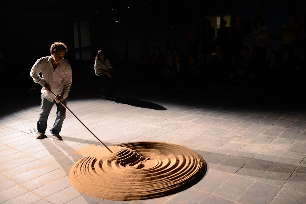 """טל רמון מבצע את """"מקום"""" של מיכה אולמן, מוזיאון ישראל, נקודת מגע 2013. מיצג עם ערימת חול ומטאטא"""