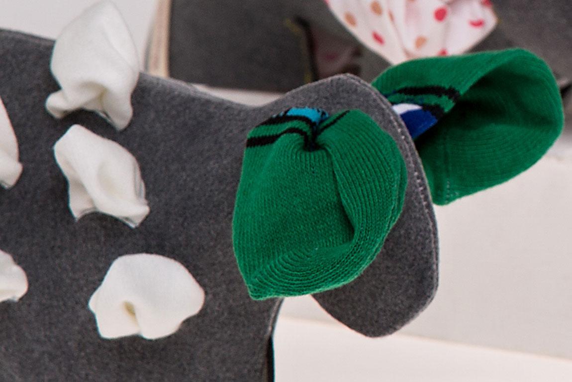 """puppetology"" (הכבשה), אודליה ג'ורנו. האוזניים הן גרביים, ובד לבן שמציץ מהפתחים האחרים הוא הצמר"