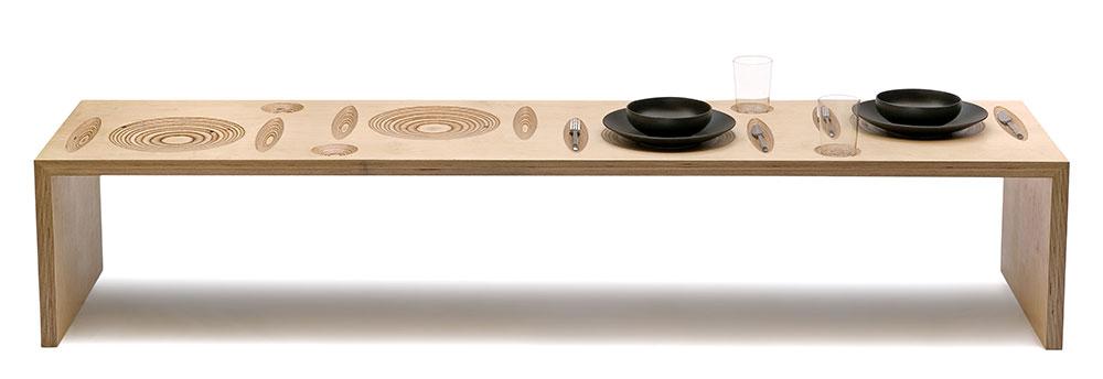 גומה. שולחן נמוך ומאורך מלביד עץ לבנה עם שקערוריות טופוגרפיות