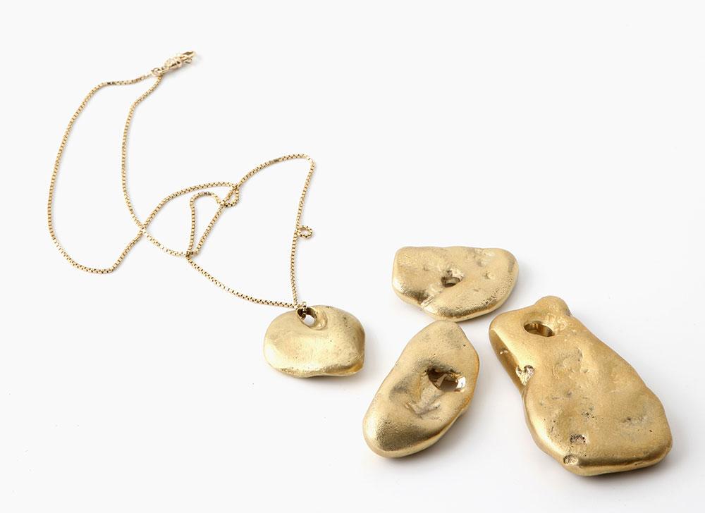 שרשרת זהב עם תליון מצופה זהב מסדרת מבוית. אבני חוף היו למודל היציקה של התליון