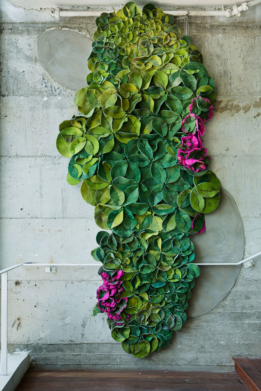 Felt Life. שטיח מודולרי (נראה כצמח מטפס עם פריחה בוורוד עז) של אריחי קיר אקוסטיים מלבד