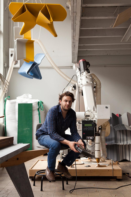 ואן דר קוי בסטודיו ליד הזרוע הרובוטית שתכנן להדפסה תלת-מימדית