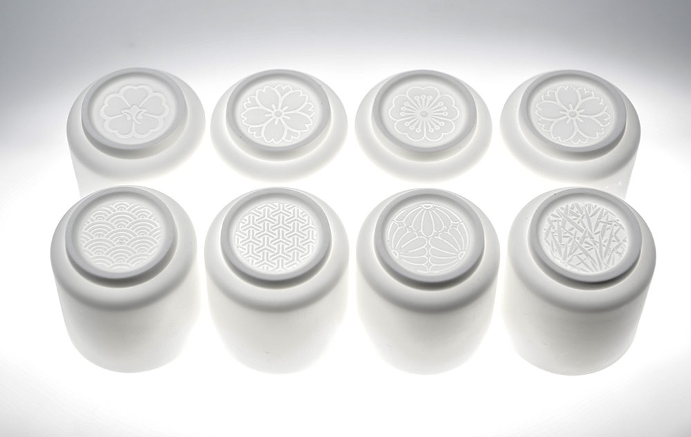 מערכת תה בהשראה יפנית. האור מדגיש את התבליט החרוט בתחתית הספל