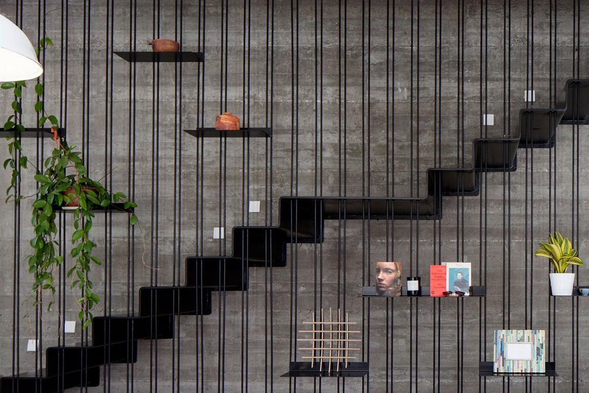 סבכת מוטות ברזל שחורים ודקים הסוגרת את חלל המדרגות משמשת למדפי ברזל קטנים תלויים. אדריכלות: דייוויד לבנטל. צילום: יעל אנגלהרט