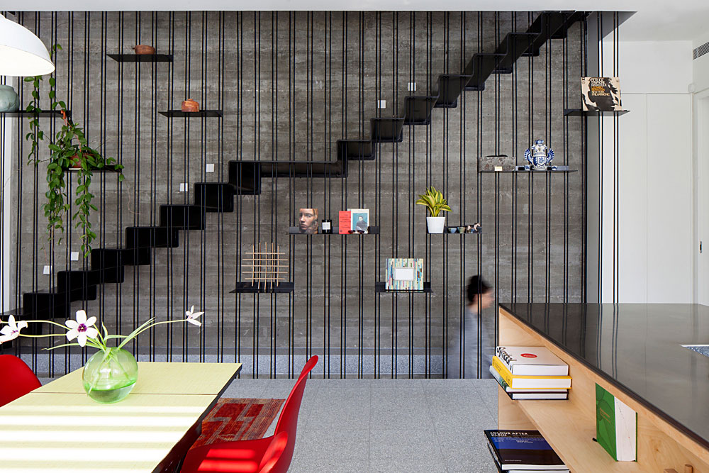 מסך מוטות ברזל שחורים משמש כמעקה גרם המדרגות. טאון האוז בביצרון. אדריכלות: דיוויד לבנטל. צילום: יעל אנגלהרט
