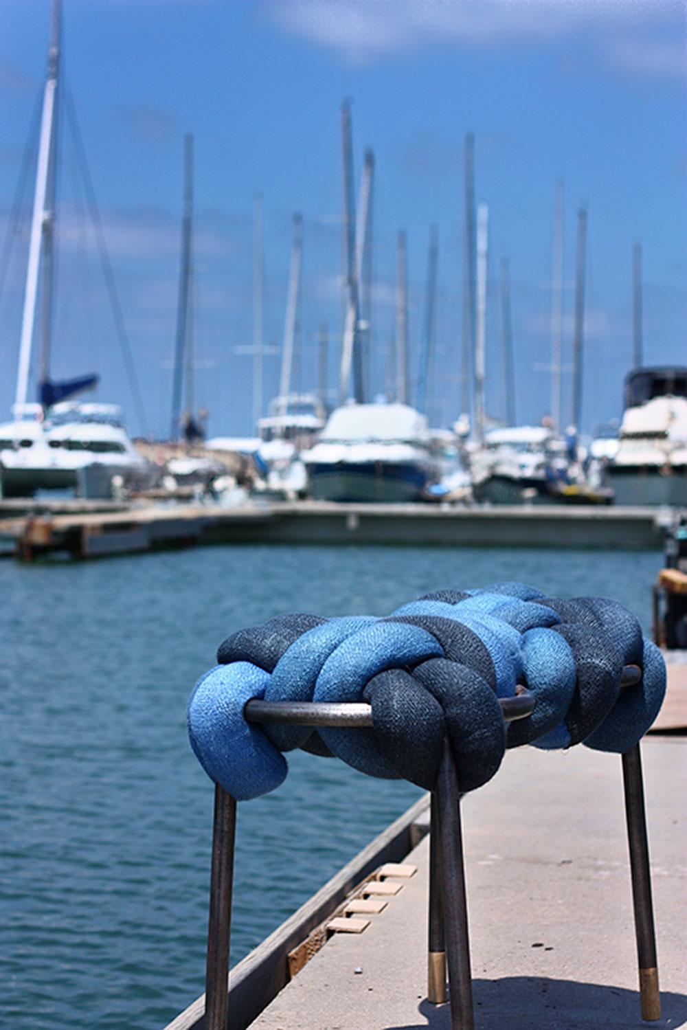 פרויקט הגמר של טסלר - מושבו של השרפרף עם מסגרת המתכת קלוע מגלילי טקסטיל בתלכלת וכחול על רקע הסירות במעגן נמל יפו