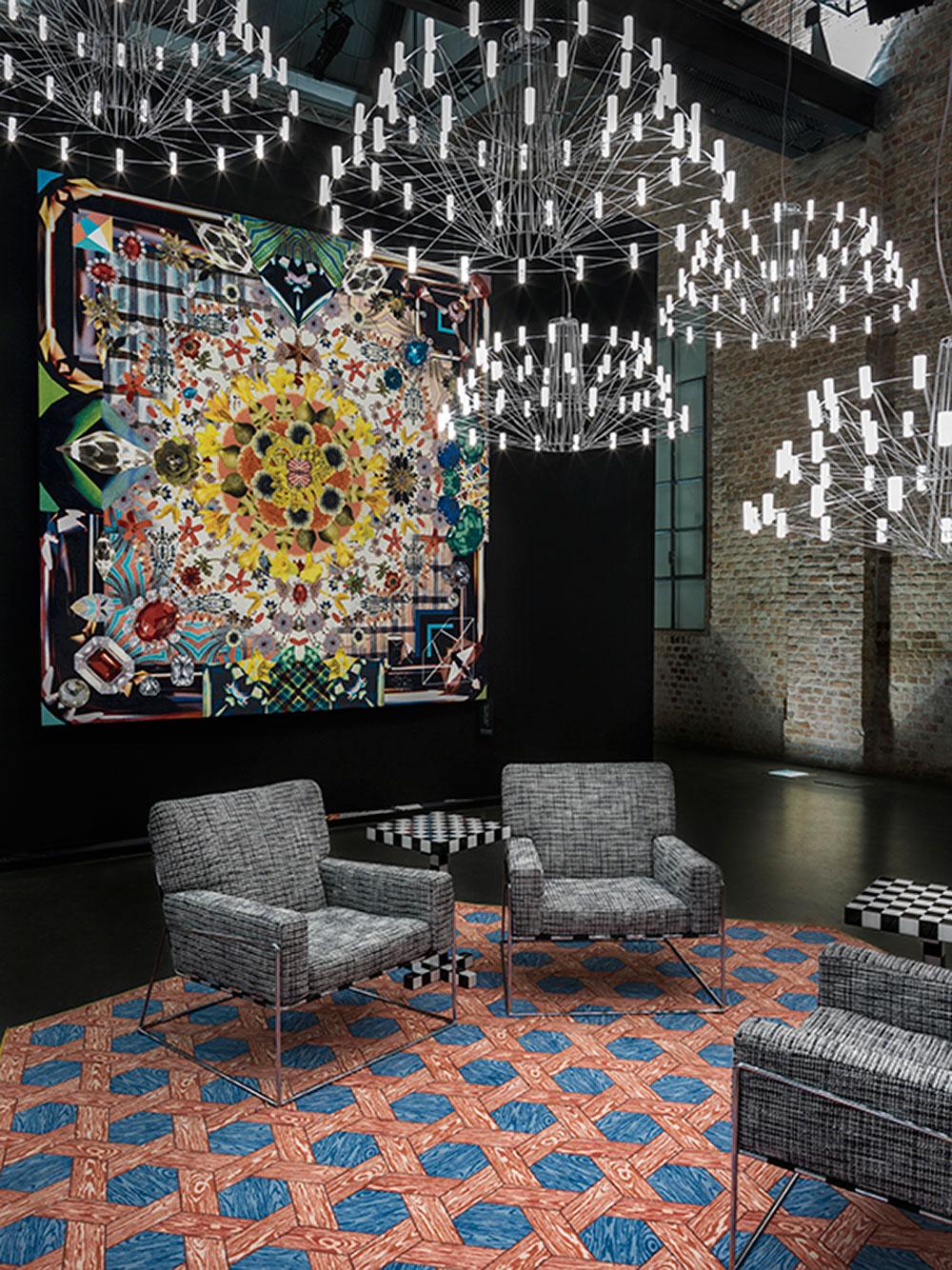 מנורות Coppélia בעיצוב Arihiro Miyake, על הקיר השטיח Jewels Garden בעיצוב בית כריסטיאן לקרואה, על הרצפה  Hexagon Red / Blue בעיצוב סטודיו יוב, ועליו כורסאות צ'ארלס