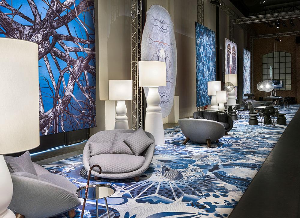 כורסאות Bart Swivel בעיצוב צוות מוי, שטיח Delft Blue של וונדרס והדפסים דיגיטליים שונים, מהם היפר ריאליסטיים תלויים ברקע