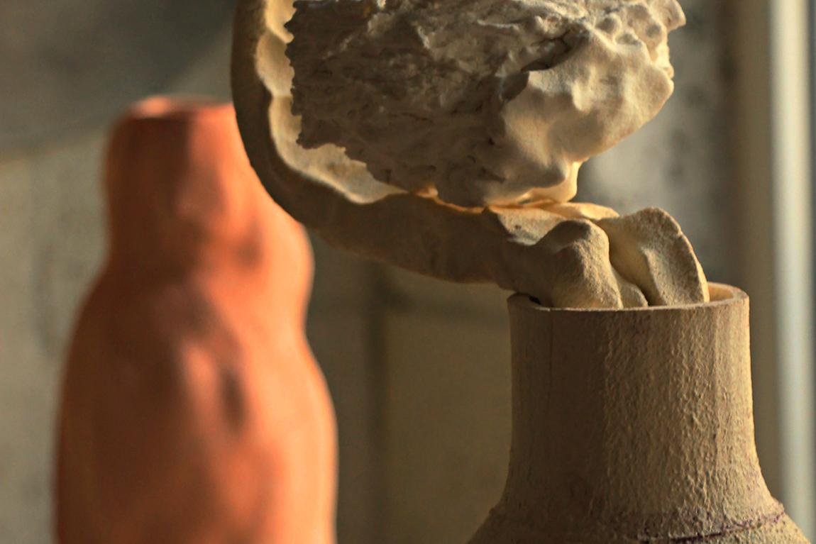 """יותר מכל יעל עצמוני אוהבת ליצור כדים וצלחות. זה לכתוב את האלף-בית של הקרמיקה, היא אומרת, ליצור את לבני הבניין. הם הבסיס, האותיות הראשוניות, חפצים שמתקשרים מקום, זמן, שימוש. ועם זאת יש בהם מימד שהוא מעבר לשימושיות כאובייקט אמנותי, פסל. מהכדים הנוכחיים שלה מזדקרות פה ושם חתיכות חמר, בבחינת עצמים בלתי מזוהים. גם הן, היא אומרת, סוג של אותיות ראשוניות, שמטרתן העיקרית לעורר שאלות. כרגע השאלות נותרות פתוחות, אבל הן קרקע לתחביר שעצמוני כבר מתכוונת לחבר איתן ואליהן בהמשך. לא מזמן חזרה עצמוני, אמנית קרמיקה ומרצה בכירה במחלקה לקרמיקה וזכוכית בבצלאל, משהות-אמן ב- EKWCבדן בוס שבהולנד. גוף העבודות שהיא מציגה בתערוכה היחיד כד ורוד צלהב שאצרה אירנה גורדון ומוצגת בימים אלה בבית האמנים בתל-אביב, החל שם. בהולנד עבדה גם על כדי ענק, מעין ארכיטיפים של אמא ואבא. אחד מהם יוצג בהמשך החודש בבית-בנימיני. ב""""שרטוטי שיכחה"""", תערוכת היחיד שהציגה בגלריה פריסקופ לפני שנתיים, חזרה עצמוני אל סוביבור, מחנה ההשמדה שממנו ניצל אביה, דב פרייברג. את זיכרונותיו מהתקופה ההיא העלה האב על הכתב בספר """"השריד מסוביבור"""". בעבודה רחבת ההיקף של בתו, התלכדו מדע הארכיאולוגיה ומעשה האמנות לעיסוק בהווה, בזיכרון, בשיכחה, במחיקה. העיסוק בעבר, הקרוב והרחוק, קיים גם בתערוכה הנוכחית, אבל אליו נארגות מחשבות על העתיד. על הילדות המורכבת של זמננו, על המסרים שלאורם אנחנו חיים ואותם אנחנו מעבירים הלאה, על הילדים של היום שיהיו המבוגרים של מחר. עצמוני מציגה קבוצת צלחות ושלוש סדרות כדים. אף לא אחד מהם נעשה באופן שבדרך כלל היא יוצרת כדים וצלחות - על האובניים. הפעם היא השתמשה בתבניות שסיפקו נקודת מוצא זהה לכל יצירי כפיה, בעוד שהאובייקטים הסופיים שונים זה מזה באופן ניכר. הצלחות מתפקדות ספק כמעין ירחים בחלל, ספק כצלחות מעופפות, אולי צלחות לוויין - אובייקטים שמימיים המביטים מלמעלה, מהגובה. עצמוני מספרת שהיה לה חשוב ליצור אותן מפורצלן, ולחרוט בהן את טביעות אצבעותיה. קבוצת כדים אחת קשורה לסיפור הבסיסי של כד. """"יש לה צוואר ורגל ומה שביניהם"""". את הכדים בנתה כפלחים, שאפשרו לה לעשות שינויים במבנה הזורם. על הכדים ציירה ורשמה רישומים של ילדים וכלבים. """"עם כל החמידות והמתיקות, אפשר לזהות בהבעות פניהם של הילדים בגרות וכעס. קצת ממה שאני מרגישה כלפי גידול """