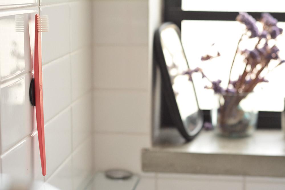 מברשת שיניים אדומה על קיר חדר רחצה