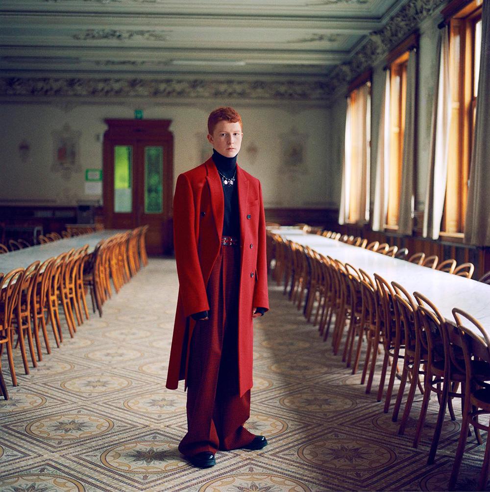 נער לבוש מעיל אדום ארוך באולם אוכל מפואר