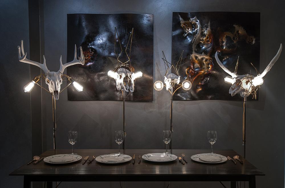 """את מיצב """"הסעודה הפרימיטיבית"""" הציגו Eetu Enqvist ו-Nino Hynninen מסטודיו Paja&Bureau בשבועות העיצוב של מילנו, פריז והלסינקי. גופי התאורה משלבים גולגלות איילים, ועל הקיר עבודות של אנקוויסט"""