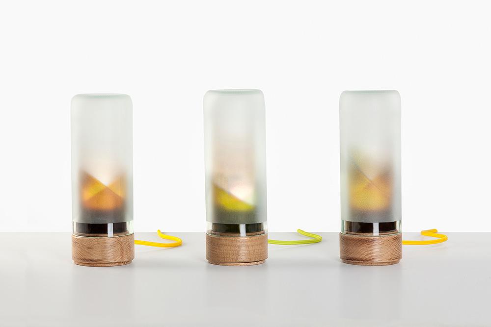 גופי התאורה של Suit-Case workshop. הבסיס עשוי עץ אלון והאהיל נוצר מהבקבוקים עם הגוונים הלא מדויקים המתקבלים בזמן החלפת צבע בקו הייצור בפניציה. צילום: עדו אדן