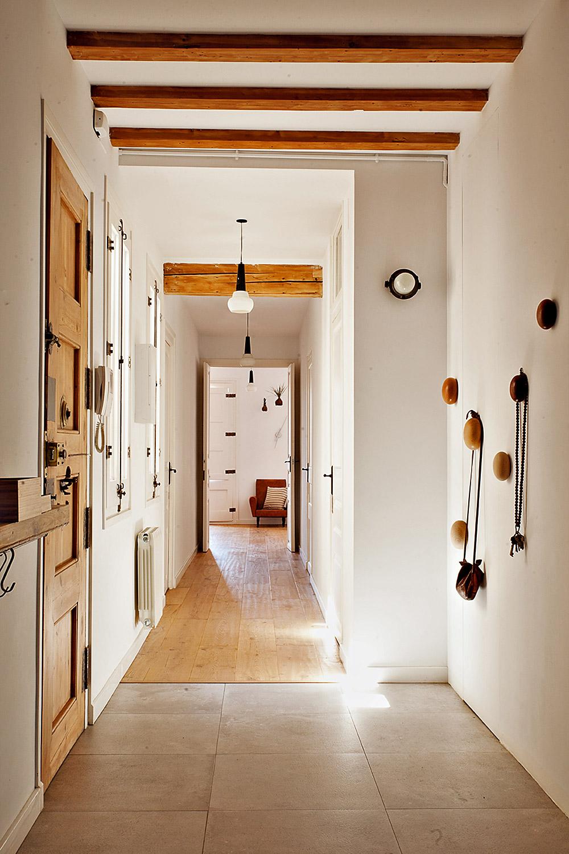 מבט אל האגף הפרטי. מימין מתלי העץ העגולים, משמאל דלת הכניסה לדירה
